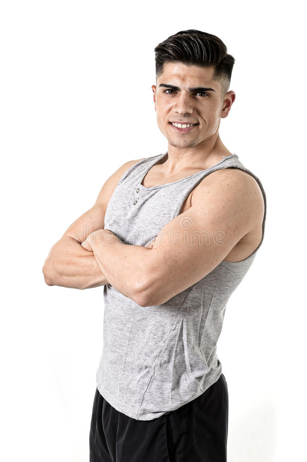 Attractive sport man with big strong athletic body posing with folded arms looking cool smiling happy. Young attractive sport man with big and strong athletic royalty free stock photography