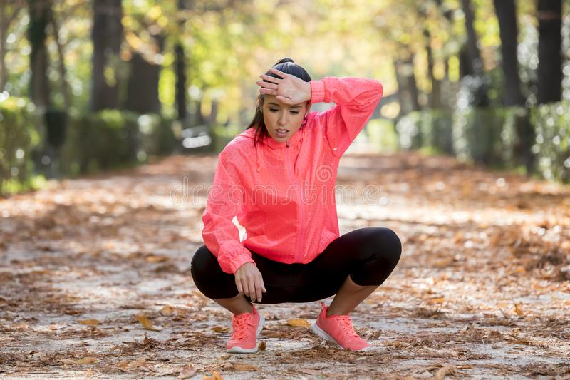 Attractive sport woman in runner sportswear breathing gasping and taking a break tired and exhausted after running workout on Autu. Young beautiful and royalty free stock images