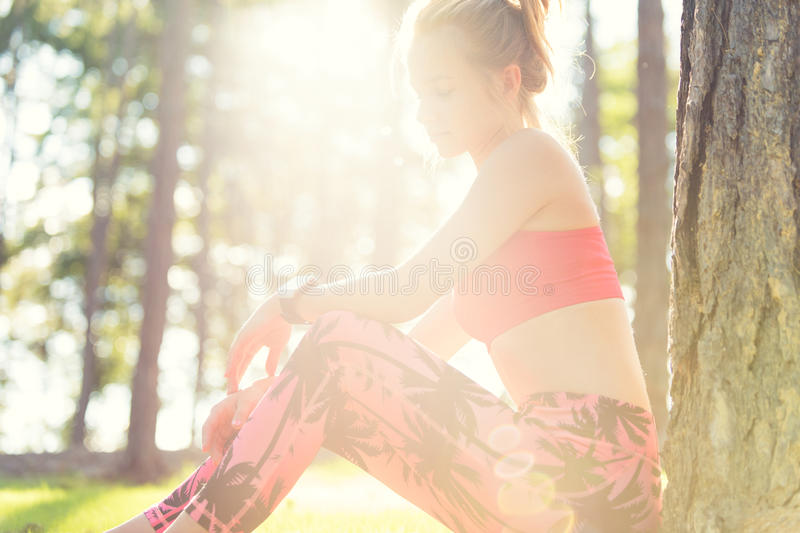 Attractive sportive woman wearing smart watch taking a break after workout session. Lifestyle image with strong lens flare. Attractive sportive woman wearing stock photos