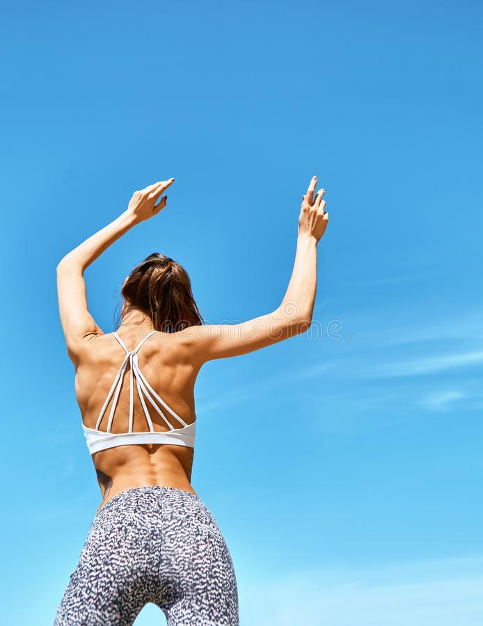 Attractive sports woman with tanned fit body posing with raised arms against blue sky at hot sunny summer day. back wiew stock image