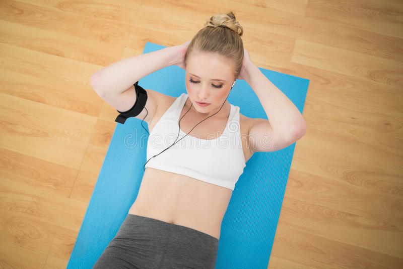 Attractive sporty blonde listening to music and exercising stock photography