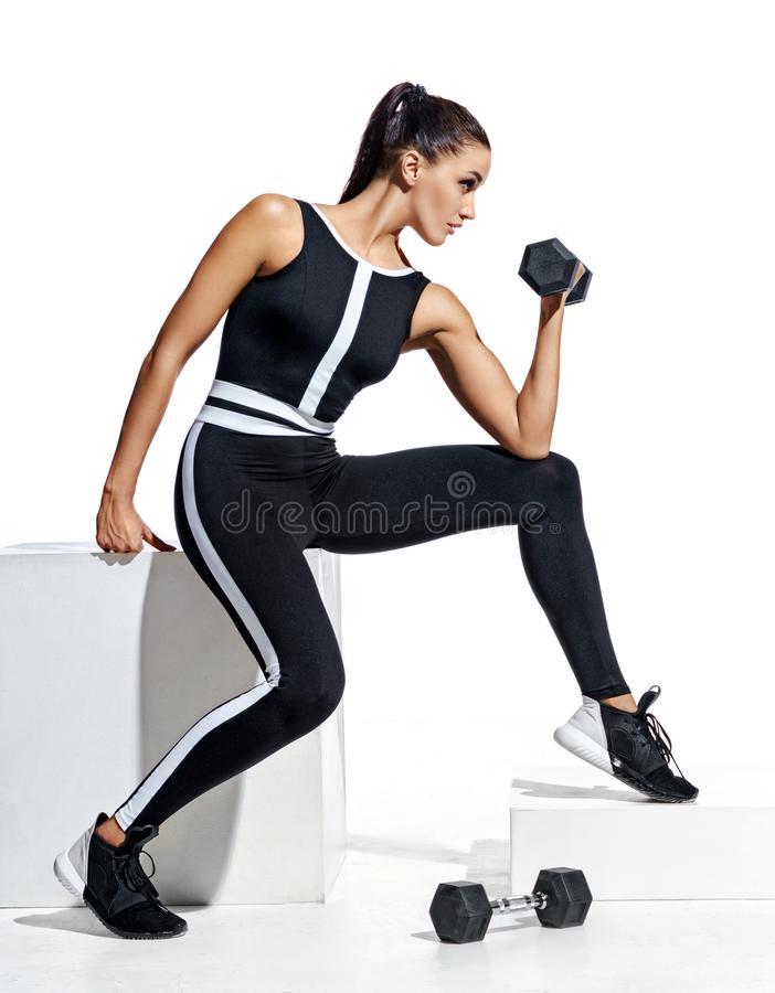 Attractive sporty girl doing exercises with dumbbells at biceps stock image