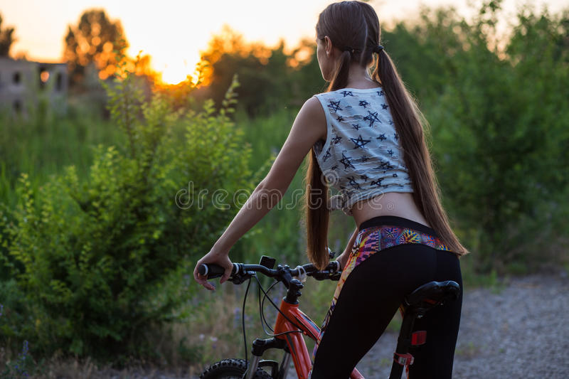 Attractive sporty girl with long hair on a bicycle on sunset royalty free stock images