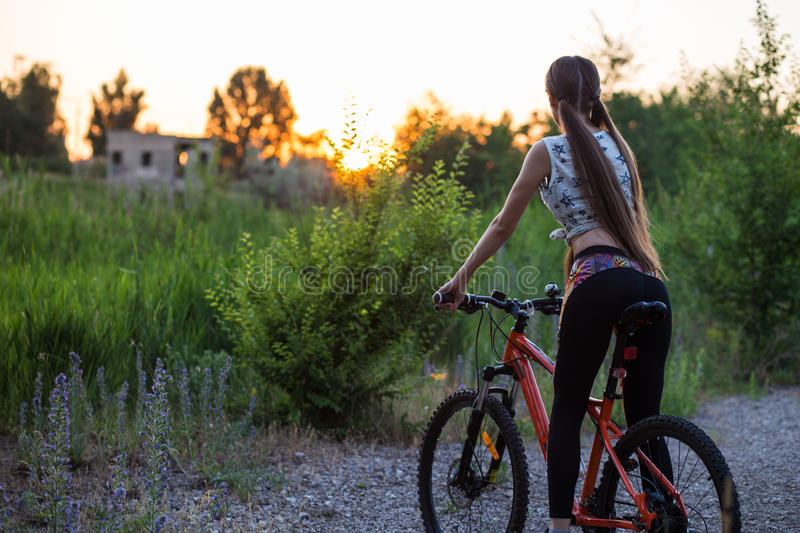 Attractive sporty girl with long hair on a bicycle on sunset royalty free stock photo