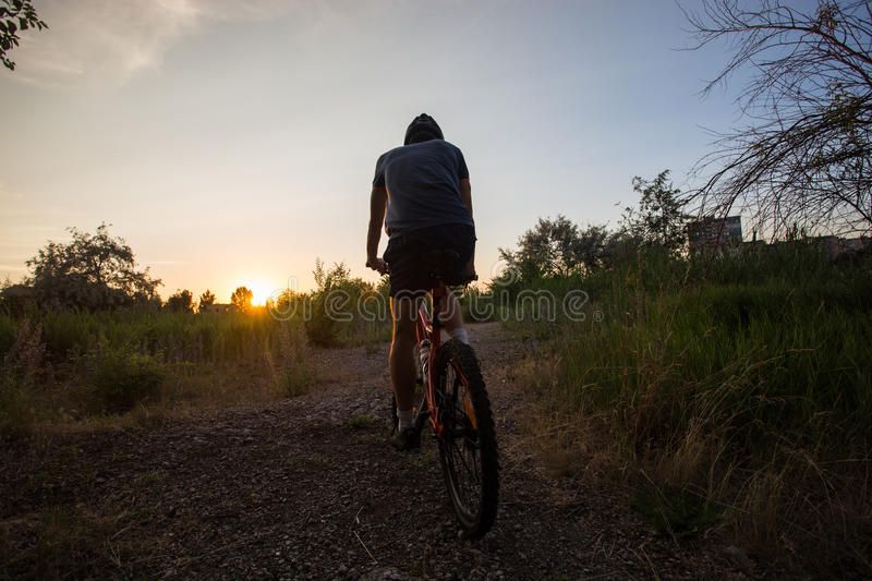 Attractive sporty girl with long hair on a bicycle on sunset stock photos