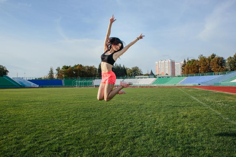 Attractive sporty happy brunette woman in pink shorts and top makes a high jump in sun rays at the stadium royalty free stock photography