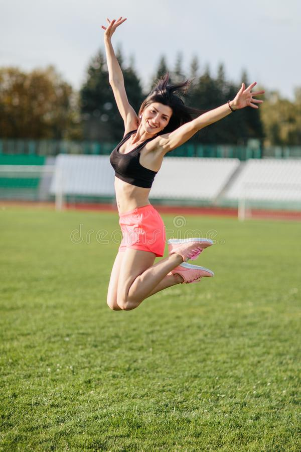 Attractive sporty happy brunette woman in pink shorts and top makes a high jump in sun rays at the stadium looking at the camera stock images