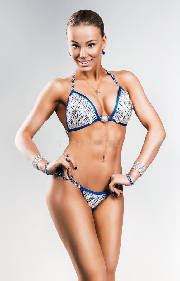 Attractive sporty smiling woman in bikini. In studio stock photography