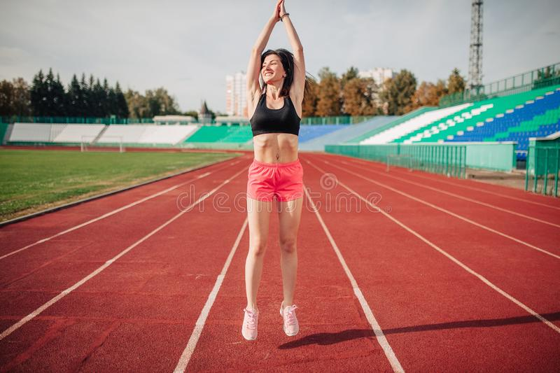 Attractive sporty brunette womang girl doing workout with jump rope in sun rays at the stadium royalty free stock photos