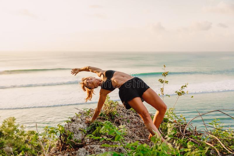 Attractive sporty woman doing yoga in outdoor at sunset and ocean on background royalty free stock photography