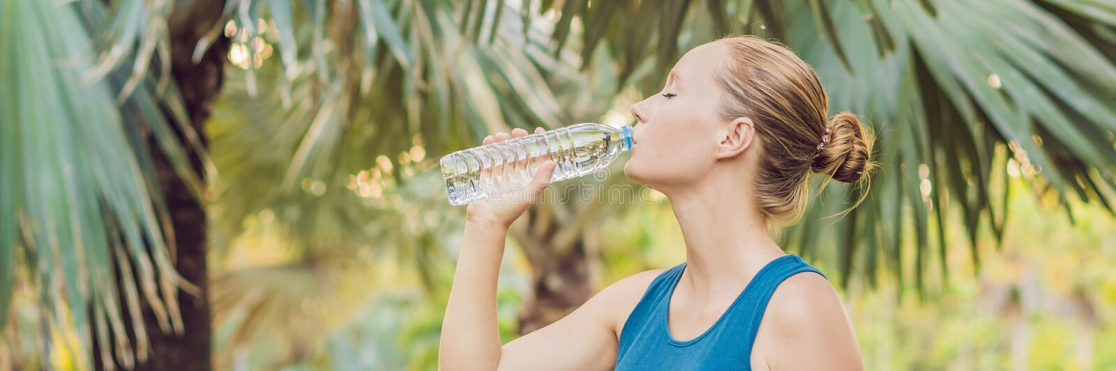 Attractive sporty woman drinking water from a bottle after jogging or running BANNER, long format. Attractive sporty woman drinking water from a bottle after royalty free stock photo