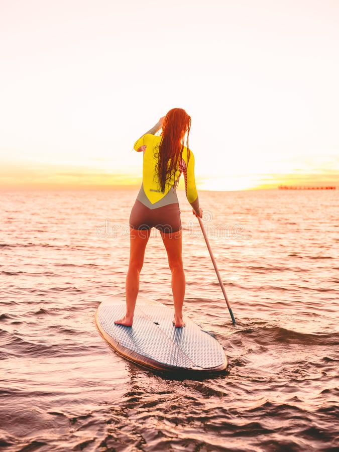Attractive sporty woman stand up paddle surfing with beautiful sunset or sunrise colors. Attractive sporty woman stand up paddle surfing with beautiful sunset or stock images