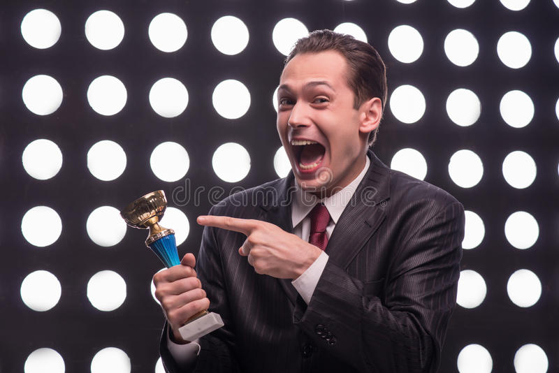 Attractive star TV presenter. Half- length portrait of excited young man wearing great black suit and vinous tie standing behind the rostrum holding the Oscar stock photos