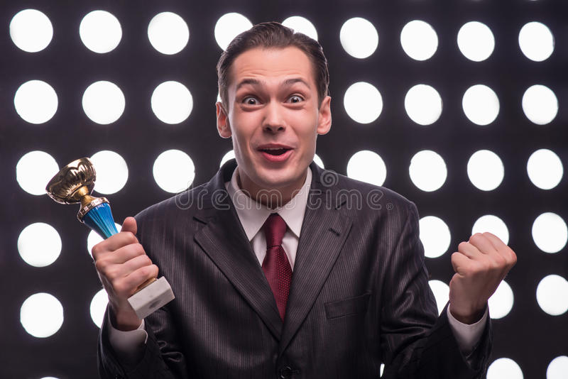 Attractive star TV presenter. Half- length portrait of excited young man wearing great black suit and vinous tie standing behind the rostrum holding the Oscar royalty free stock image