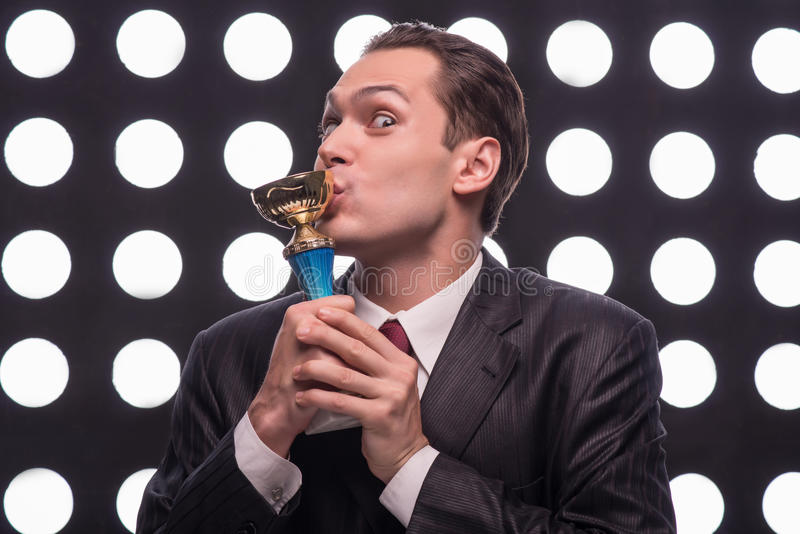 Attractive star TV presenter. Half- length portrait of excited young man wearing great black suit and vinous tie standing behind the rostrum kissing the Oscar royalty free stock images