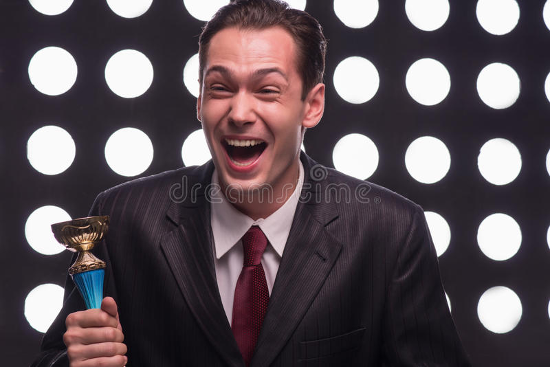 Attractive star TV presenter. Half- length portrait of handsome excited man wearing great black suit and vinous tie standing aside behind the rostrum holding the stock image