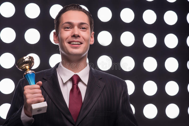 Attractive star TV presenter. Half- length portrait of handsome excited man wearing great black suit and vinous tie standing aside behind the rostrum holding the royalty free stock image