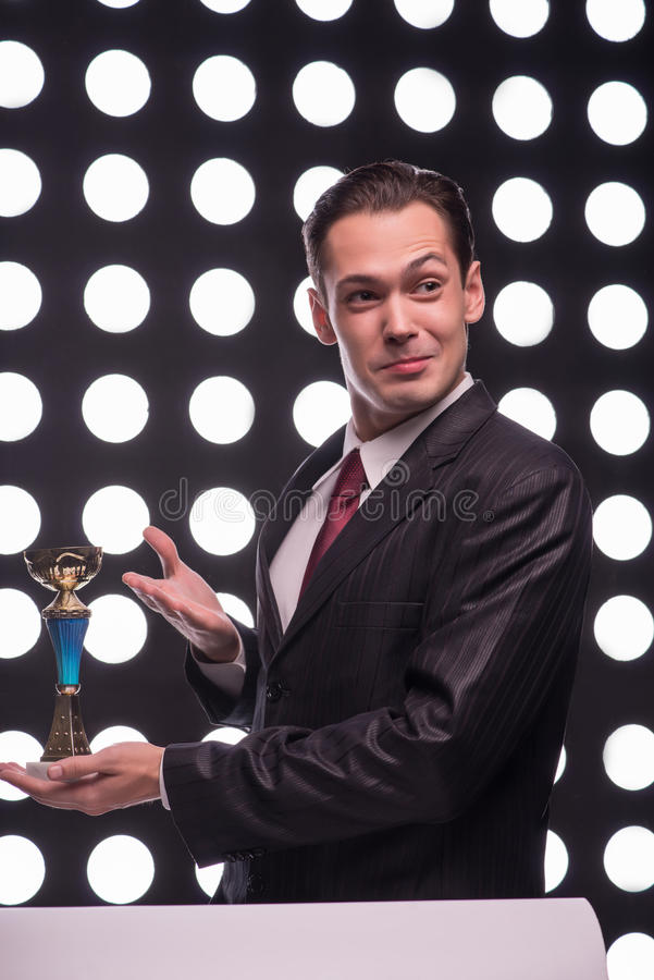 Attractive star TV presenter. Half- length portrait of handsome smiling man wearing great black suit and vinous tie standing aside behind the rostrum showing us stock image