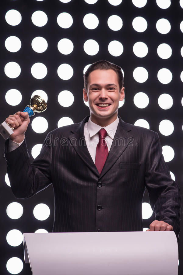 Attractive star TV presenter. Half- length portrait of handsome smiling man wearing great black suit and vinous tie standing behind the rostrum satisfied with stock image