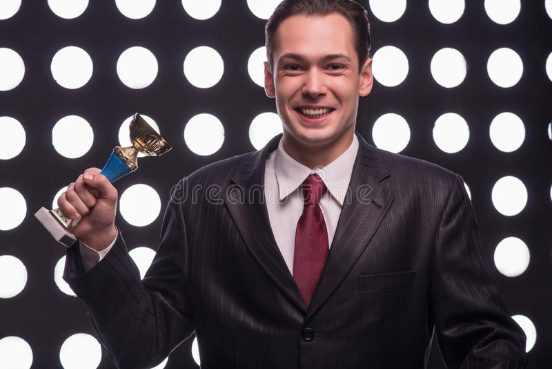 Attractive star TV presenter. Half- length portrait of handsome smiling man wearing great black suit and vinous tie standing behind the rostrum satisfied with royalty free stock photos
