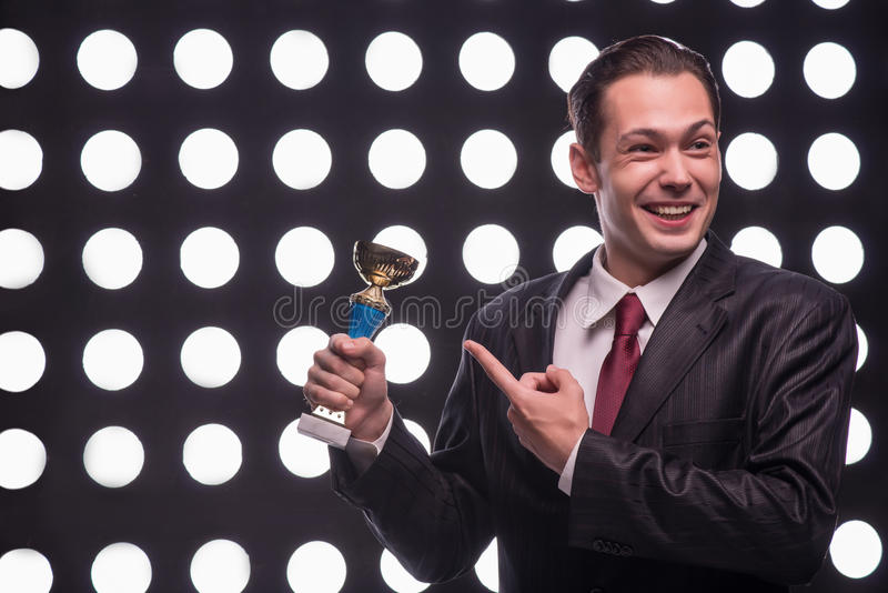 Attractive star TV presenter. Half- length portrait of handsome smiling man wearing great black suit and vinous tie standing behind the rostrum not believing stock images