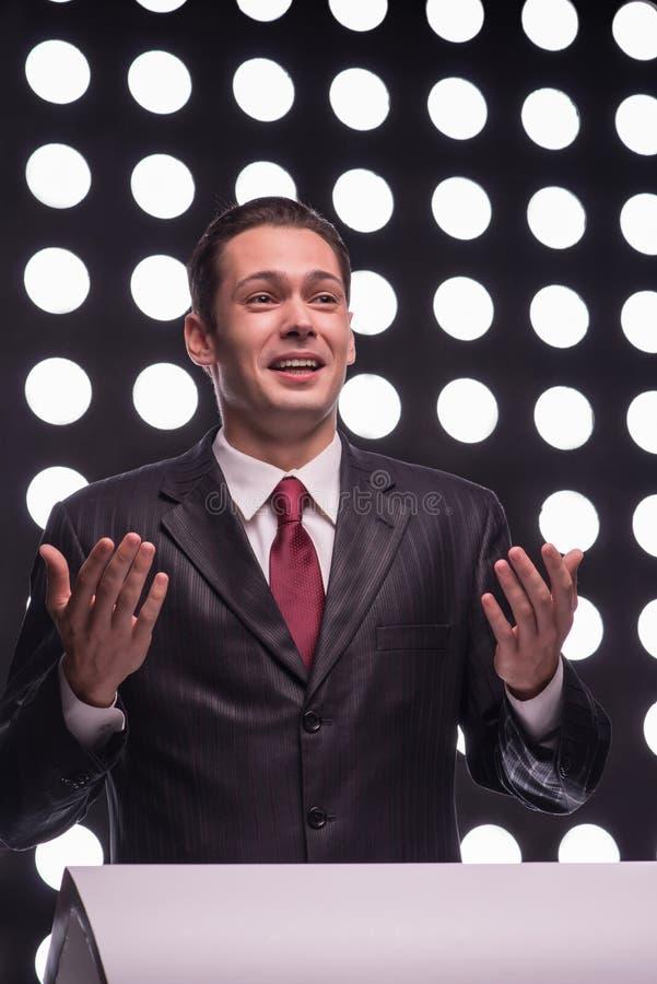 Attractive star TV presenter. Half- length portrait of handsome smiling TV presenter wearing great black suit and vinous tie standing behind the rostrum speaking stock photography