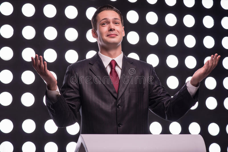 Attractive star TV presenter. Half- length portrait of handsome smiling TV presenter wearing great black suit and vinous tie standing behind the rostrum speaking royalty free stock images