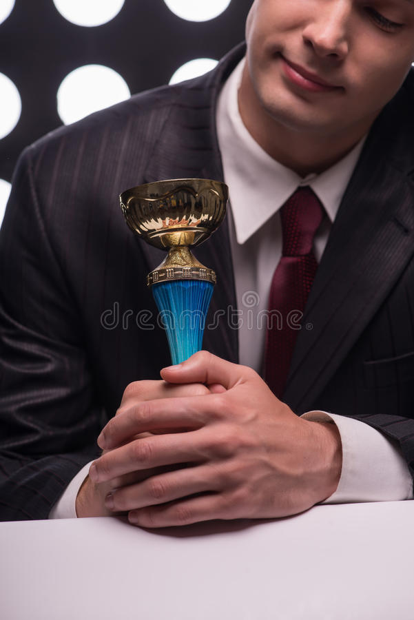 Attractive star TV presenter. Half- length portrait of handsome young man wearing great black suit and vinous tie standing and looking the Oscar statuette stock photography