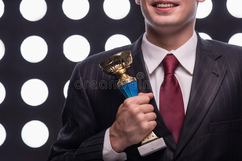Attractive star TV presenter. Half- length portrait of handsome young smiling man wearing great black suit and vinous tie holding the Oscar statuette royalty free stock image