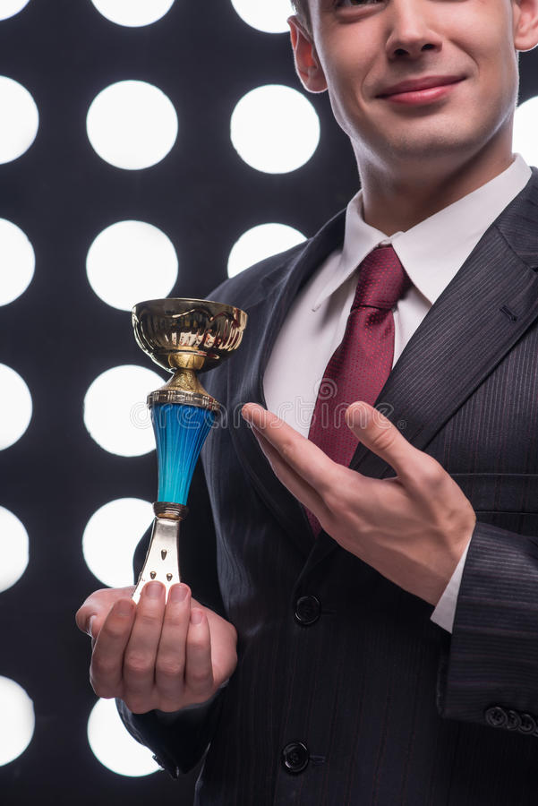 Attractive star TV presenter. Half- length portrait of handsome young smiling man wearing great black suit and vinous tie holding the Oscar statuette stock image