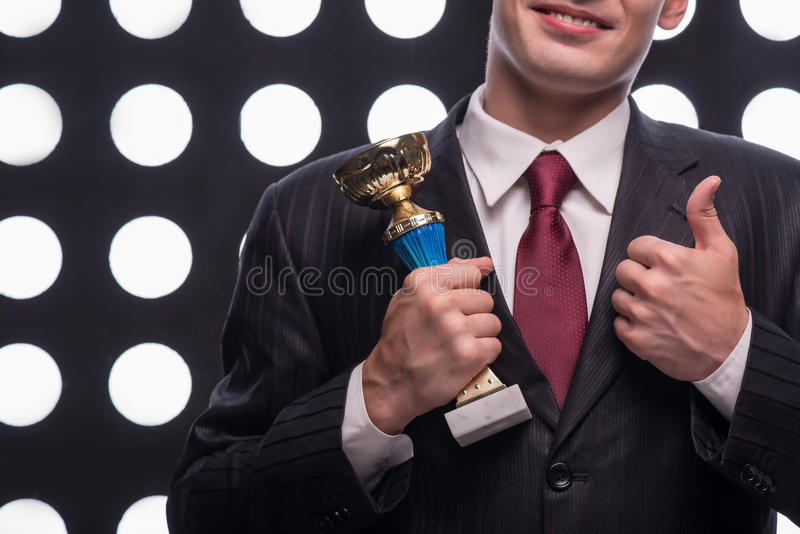 Attractive star TV presenter. Half- length portrait of handsome young smiling man wearing great black suit and vinous tie holding the Oscar statuette royalty free stock photo
