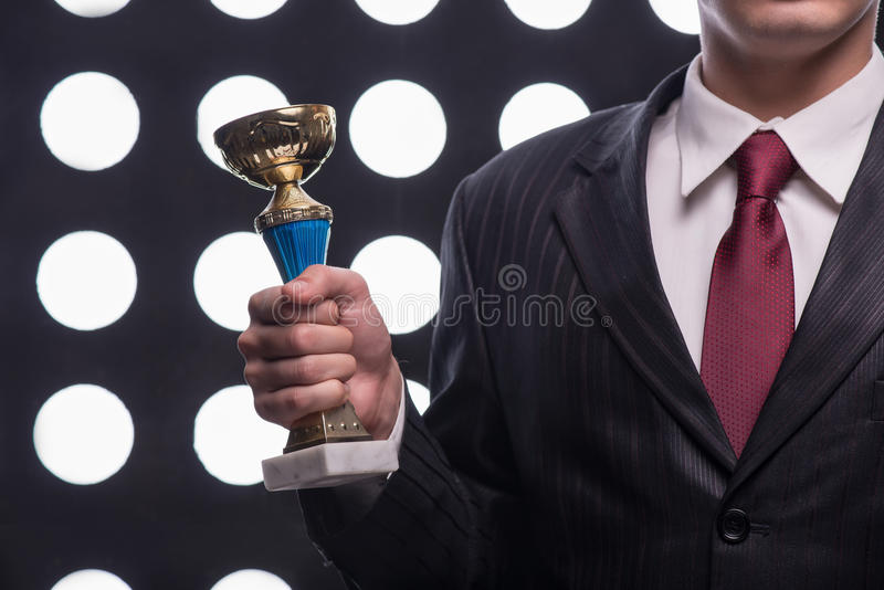 Attractive star TV presenter. Half- length portrait of the man wearing great black suit holding the Oscar statuette demonstrating us his merits royalty free stock image