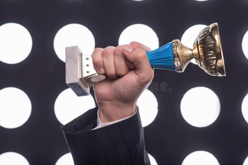 Attractive star TV presenter. Half- length portrait of the man wearing great black suit holding the Oscar statuette demonstrating us his merits royalty free stock photography