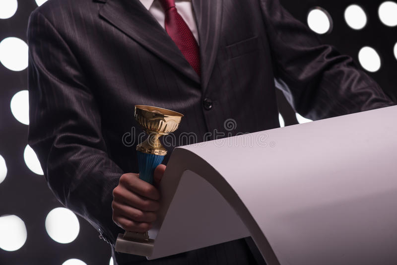 Attractive star TV presenter. Half- length portrait of the man wearing great black suit and vinous tie standing behind the rostrum holding the Oscar statuette royalty free stock photos