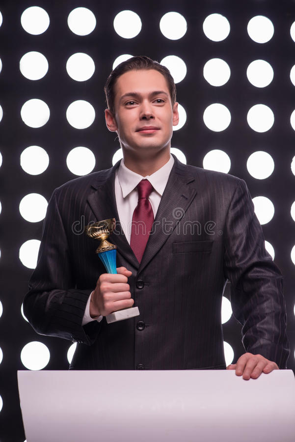 Attractive star TV presenter. Half- length portrait of smiling young man wearing great black suit and vinous tie standing behind the rostrum holding the Oscar stock images