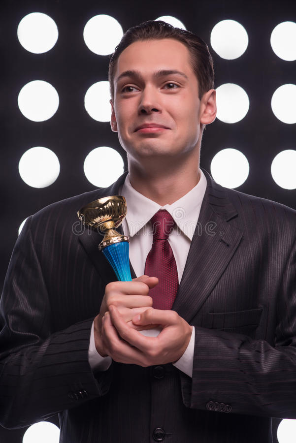 Attractive star TV presenter. Half- length portrait of smiling young man wearing great black suit and vinous tie standing behind the rostrum holding the Oscar royalty free stock image
