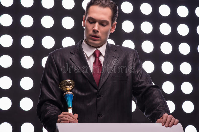 Attractive star TV presenter. Half- length portrait of thoughtful young man wearing great black suit and vinous tie standing behind the rostrum holding the Oscar royalty free stock photo