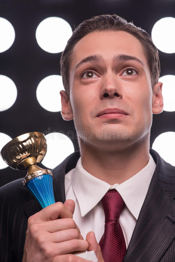 Attractive star TV presenter. Half- length portrait of young handsome happy man wearing great black suit and vinous tie holding the Oscar statuette cannot to stock photos