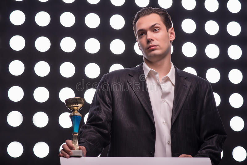 Attractive star TV presenter. Half- length portrait of young handsome man wearing great black suit holding the Oscar statuette looking at someone skeptically stock photo
