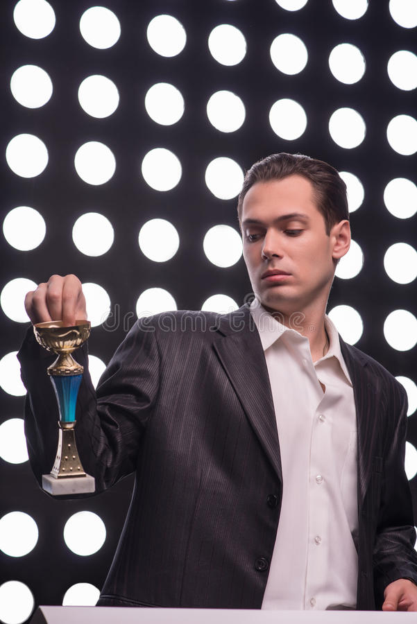 Attractive star TV presenter. Half- length portrait of young handsome man wearing great black suit holding the Oscar statuette contemptuously looking at it royalty free stock images