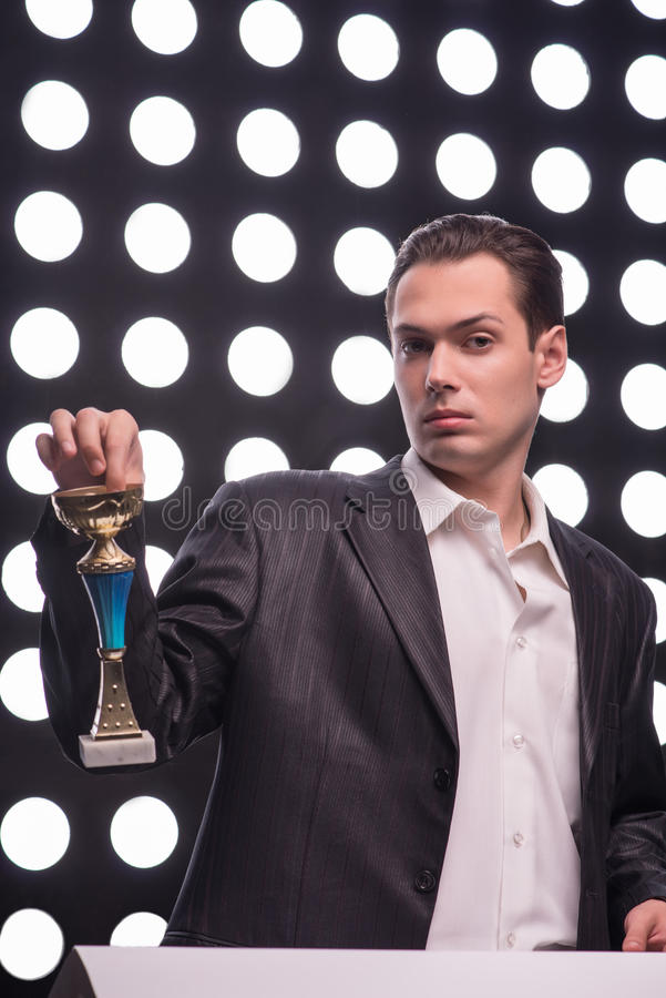 Attractive star TV presenter. Half- length portrait of young handsome man wearing great black suit holding the Oscar statuette contemptuously looking at us royalty free stock image