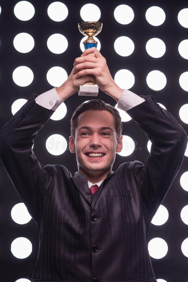 Attractive star TV presenter. Half- length portrait of young handsome smiling man wearing great black suit and vinous tie holding the Oscar statuette over his royalty free stock photography