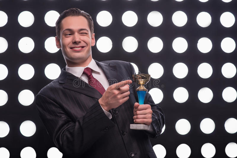 Attractive star TV presenter. Half- length portrait of young handsome smiling man wearing great black suit and vinous tie holding the Oscar statuette giving a stock photos