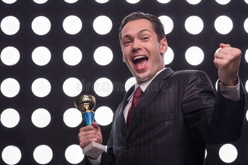 Attractive star TV presenter. Half- length portrait of young handsome smiling man wearing great black suit and vinous tie holding the Oscar statuette showing us stock photos