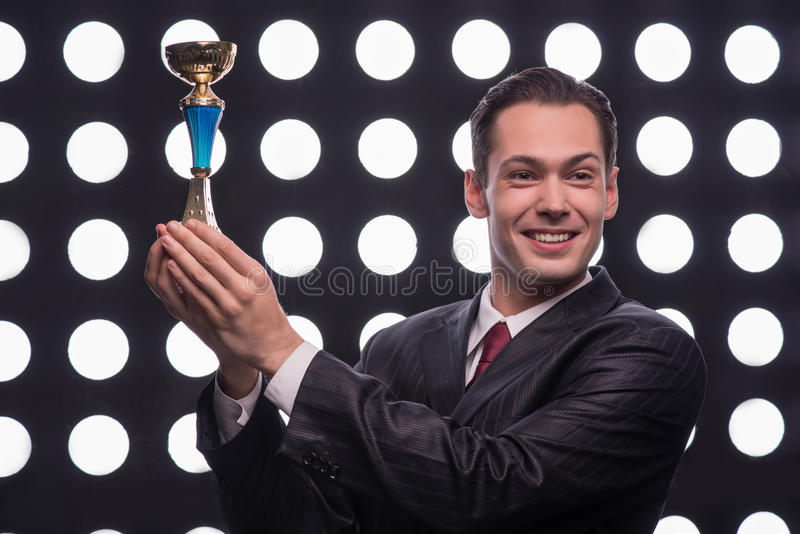 Attractive star TV presenter. Half- length portrait of young handsome smiling man wearing great black suit and vinous tie holding the Oscar statuette stock photos