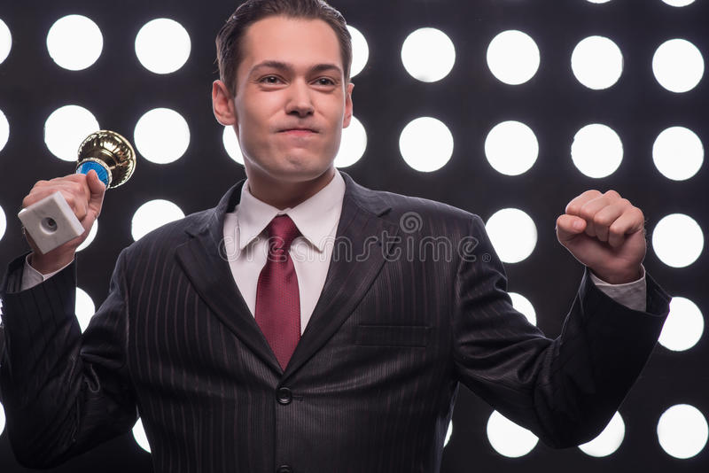 Attractive star TV presenter. Half- length portrait of young handsome smiling man wearing great black suit and vinous tie holding the Oscar statuette showing us stock image