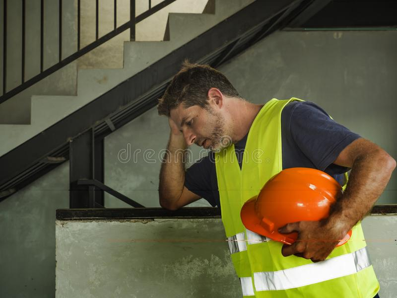 . Attractive stressed and frustrated construction worker man in vest and builder helmet looking tired and worried suffering stock images