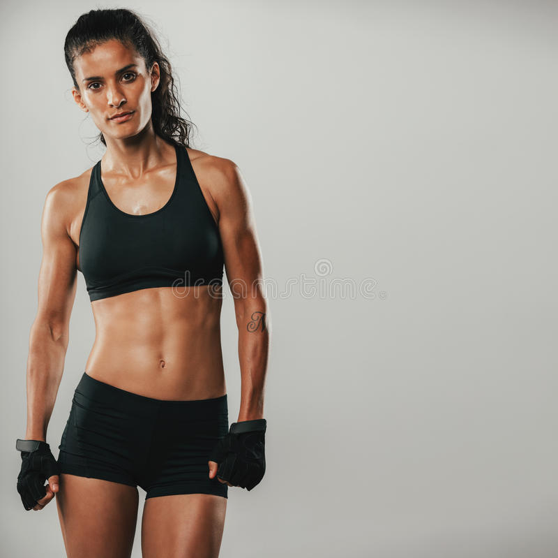 Attractive strong healthy woman in sportswear. Posing looking at the camera with a serious expression in a fitness and exercise concept royalty free stock photos