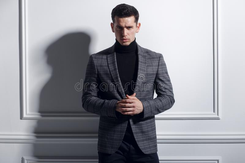 Frontal portrait of a handsome, elegant young man posing confident in stylish black-gray suit near white wall, studio. royalty free stock photos