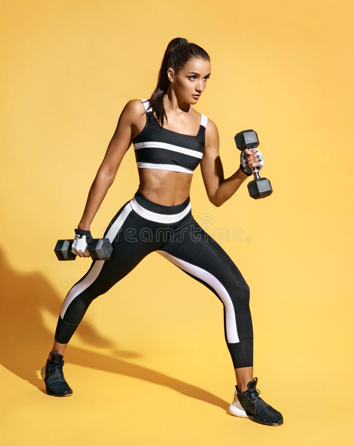 Attractive strong woman working with dumbbells. royalty free stock photography